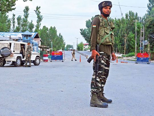 Security personnel stand guard during a lockdown in Srinagar