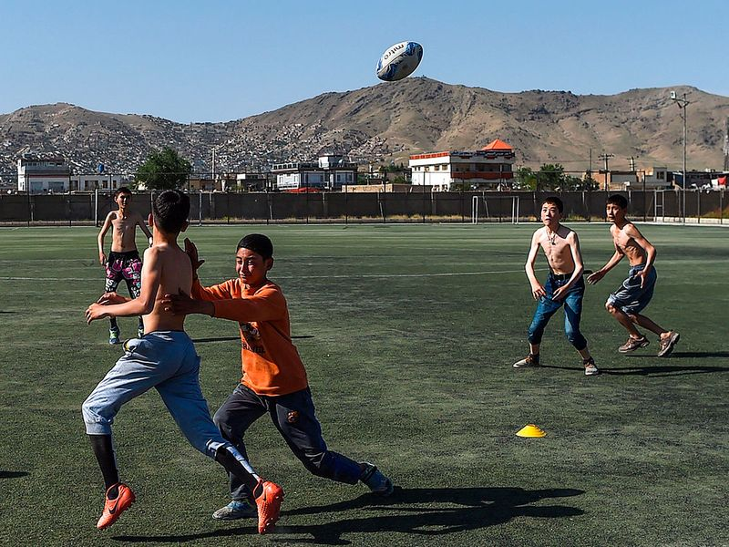 Young rugby players take part in a practice session on a pitch in Kabul