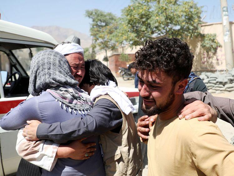 Afghan men comfort each other
