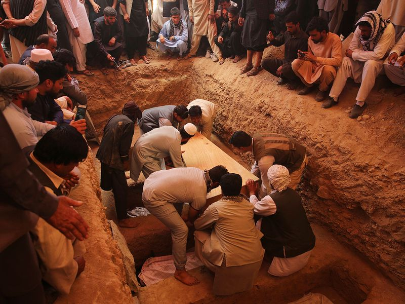 Afghans bury the bodies of victims