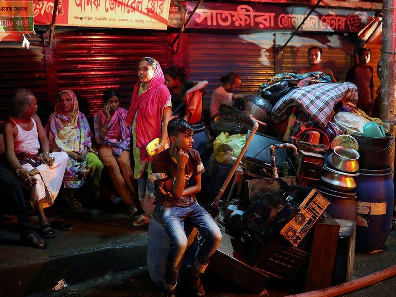 Slum dwellers sit on the street