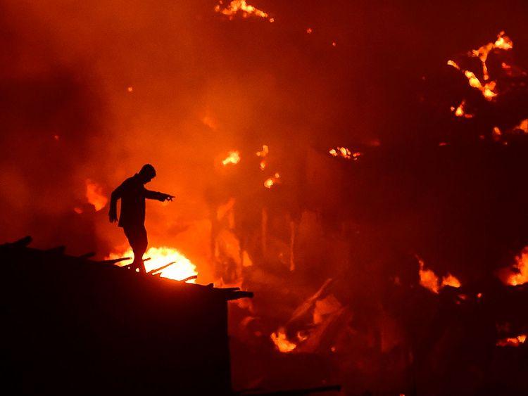a fire as a fire blazes in a slum in Dhaka
