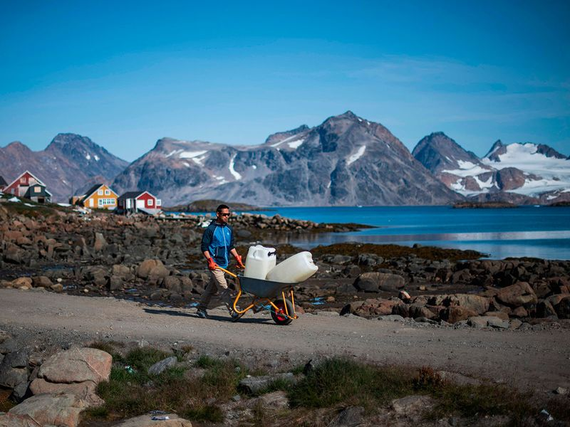 A resident of Kulusuk carts water in the town of Kulusuk, Greenland