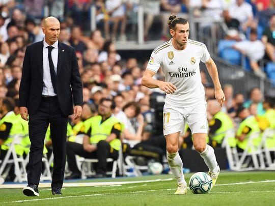 Real Madrid's coach Zinedine Zidane (L) looks at forward Gareth Bale