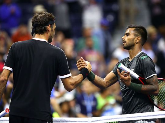 Roger Federer of Switzerland exchanges greetings with Sumit Nagal