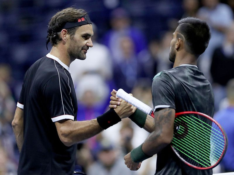 Roger Federer shakes hands with Sumit Nagal