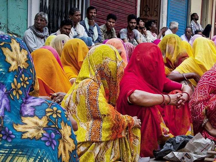 Women dressed in traditional sari dresses, attend the funeral generic