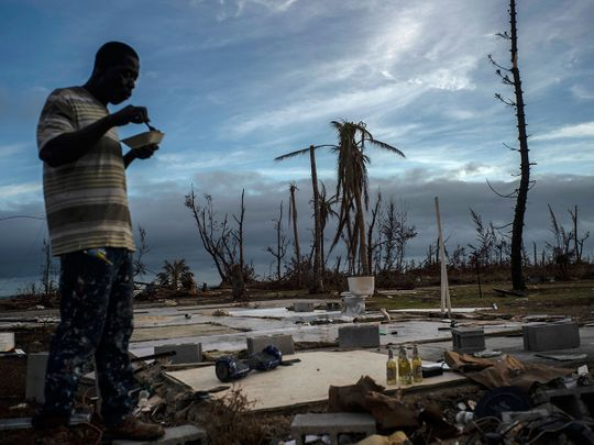 Jeffrey Roberts, 49, eats a plate of food while searching through the rubble of his relatives' home which was destroyed by Hurricane Dorian in Pelican Point, Grand Bahama, Bahamas, Saturday, Sept. 14, 2019.