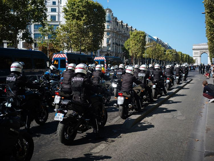 Motorcycle police officers drive along the Champs Elysees