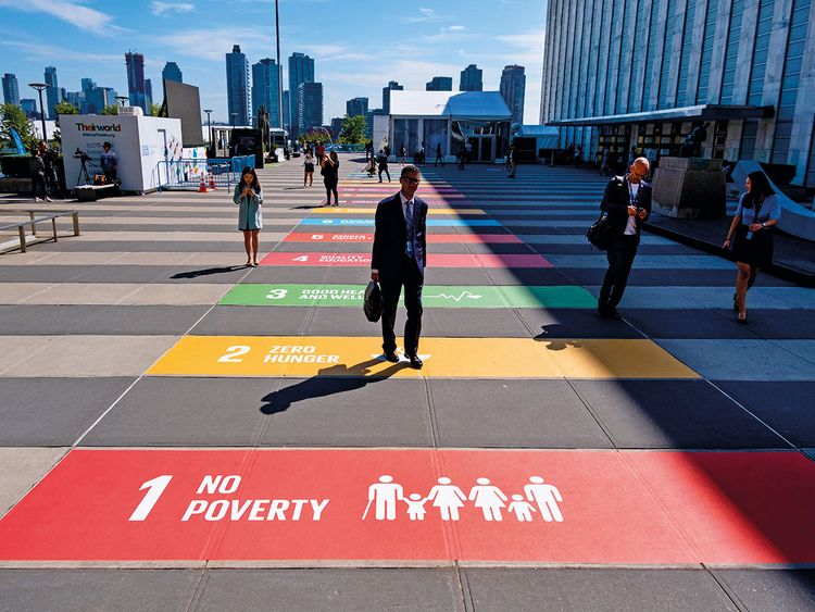 People walk along a plaza at United Nations Headquarters