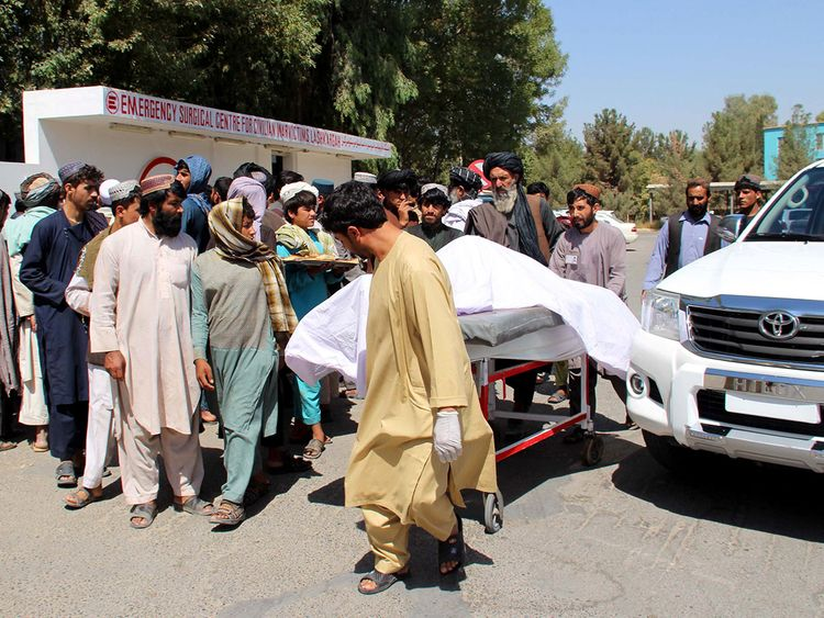 Villagers carry a dead body on a stretcher