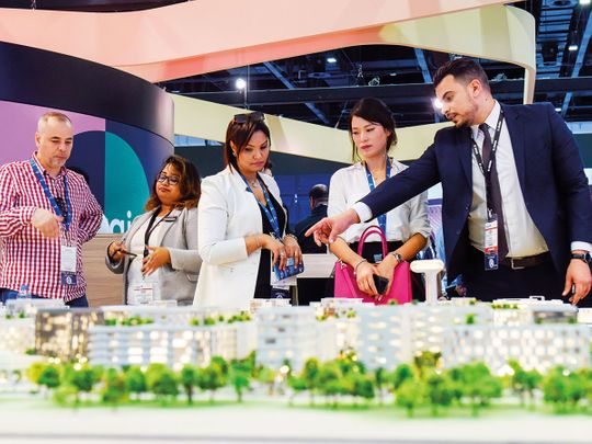Visitors looking at Aljada project in Sharjah by Arada at Cityscape Global