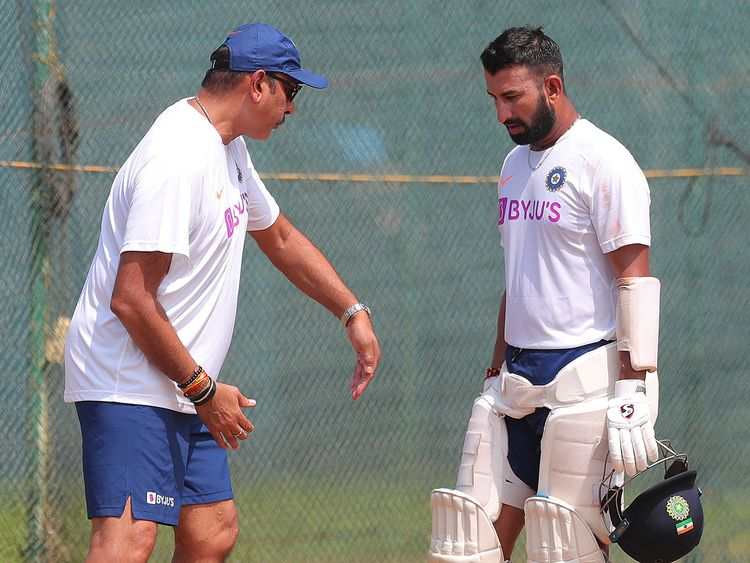 India's Cheteshwar Pujara, right listens to head coach Ravi Shastri