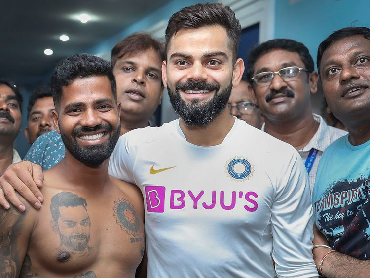 Virat Kohli poses for a photograph with his fan