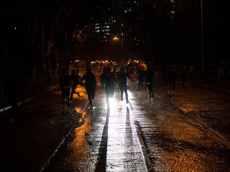 Protestors run away from police in Hong Kong, Sunday, Oct. 6, 2019.