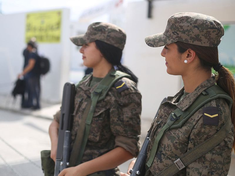 Women soldiers stand guard outside a polling station 0015151