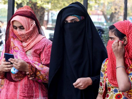 Women look on as they use mobiles phones in Srinagar