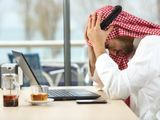 Arab man in front of laptop upset at his bank