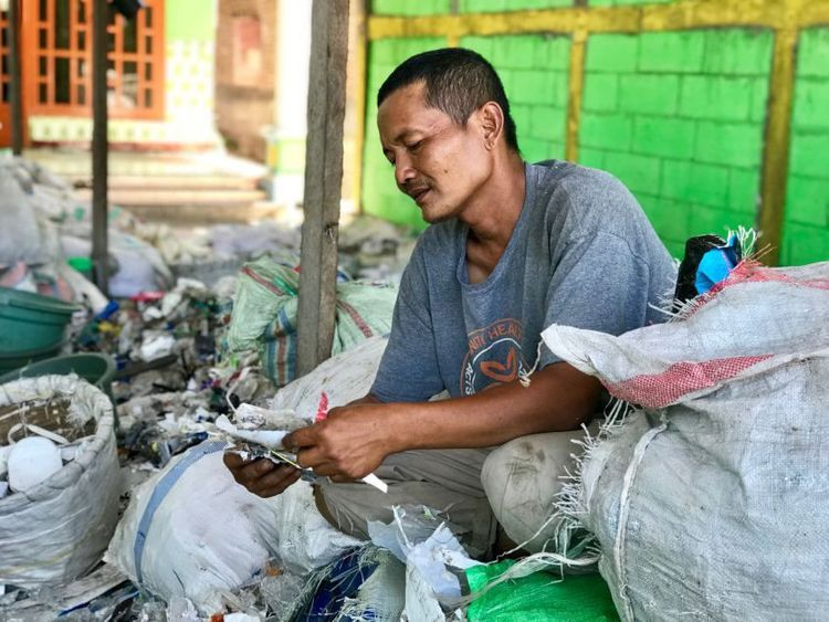 Eko Wahyudi goes through bags of recycling waste at his home facility in Bangun, Indonesia.(Shashank Bengali  Los Angeles Times)-1572020946659