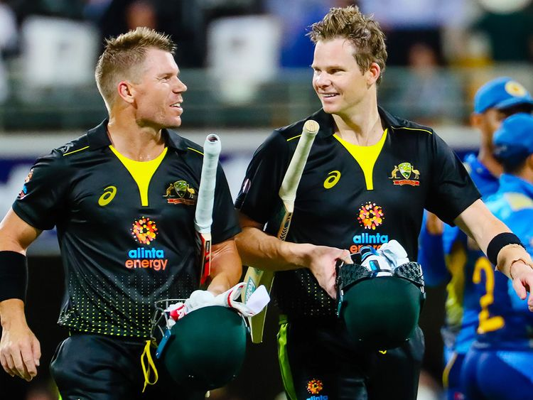 Australia's David Warner (L) speaks with Steve Smith