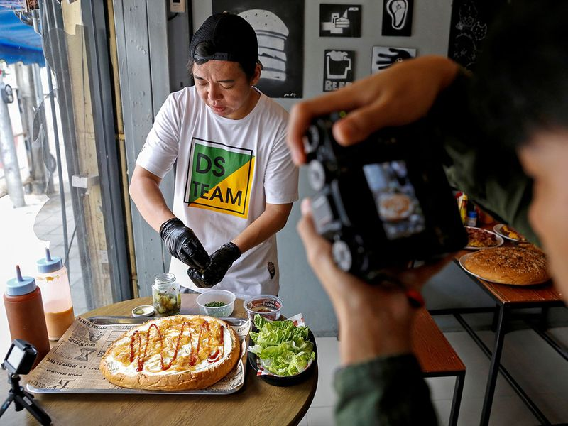 Komdech Kongsuwan, owner of the Chris Steaks & Burgers, prepares what they say is Thailand's biggest burger weighing more than 6 kilograms, before a competition held to eat it, at his restaurant in Bangkok, Thailand