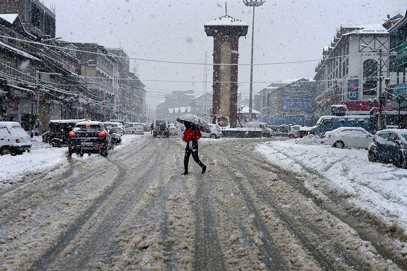A commuter moves through heavy snowfall in Lal Chowk  area of Srinagar