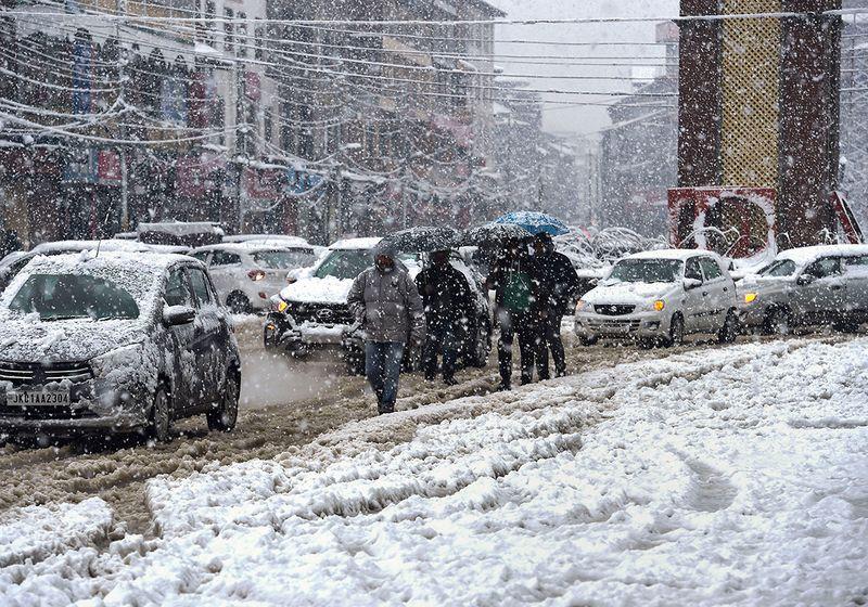 Commuters and traffic move through heavy snowfall in Srinagar