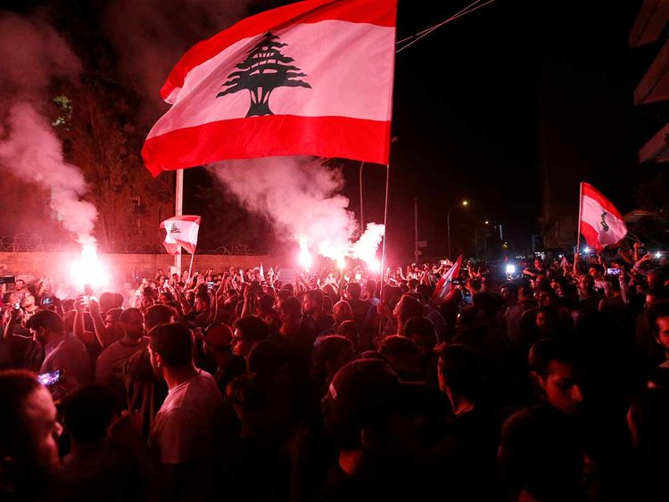 Demonstrators hold flares and Lebanese flags as they protest outside the house of former Lebanese prime minister Fouad Siniora in Beirut