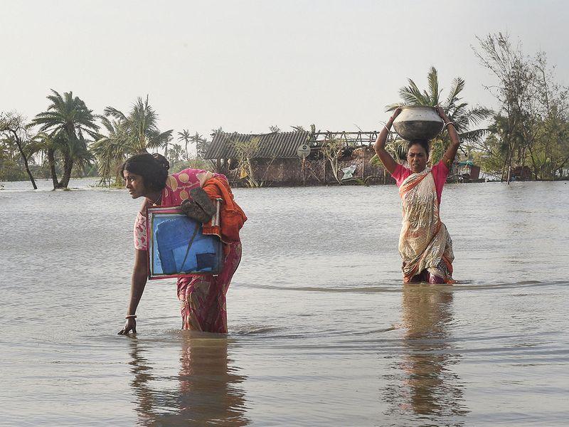 Villagers make through a flooded area at Bakkhali.