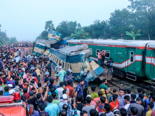 Bystanders look on after a train collided with another train
