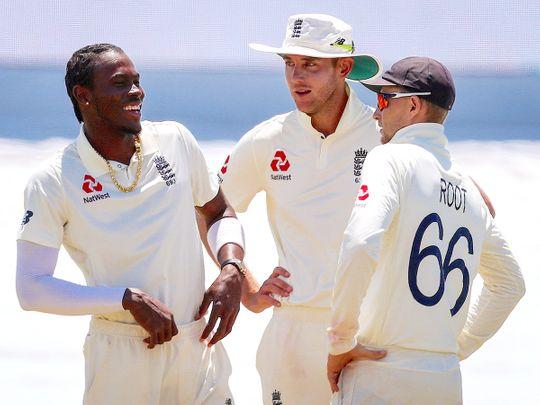 England's captain Joe Root (R) talks with teammates Stuart Broad
