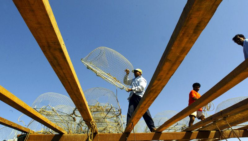 Workers arrange nets on top of a boat at Ajman fishing harbour