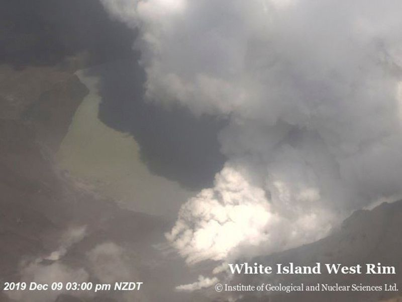 An aeriel view shows smoke billowing above the crater of Whakaari