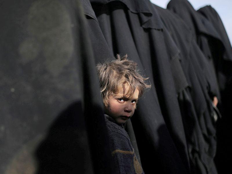 A boy looks at the camera near Baghouz, Deir Al Zor province