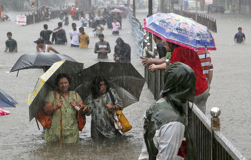 People navigate their way through a street flooded by torrential rains in Mumbai