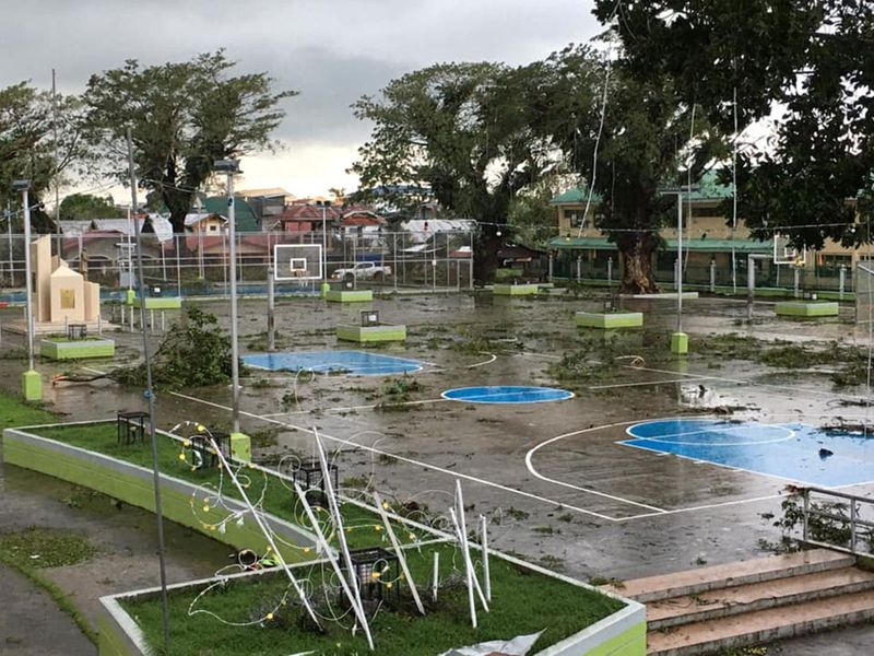 Fallen tree branches litter a basketball court after Typhoon Phanfone swept through Tanauan, Leyte, in the Philippines.