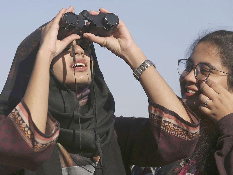 Students of Karachi University watch the solar eclipse from Karachi, Pakistan.