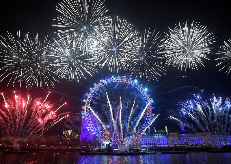 Fireworks explode around the London Eye wheel during New Year celebrations in central London, Britain.