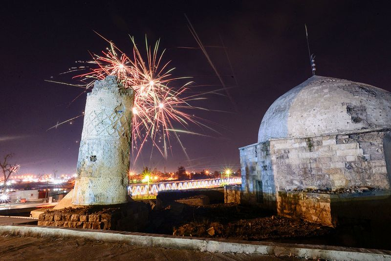 Fireworks light the sky above the Al-Aghwat Mosque as Iraqi celebrate celebrate New Year's eve in Mosul's war-ravaged old town.