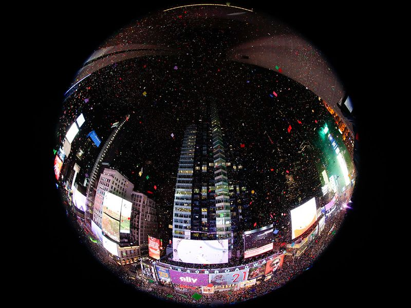 In an image taken with a fisheye lens, confetti drops over the crowd as the clock strikes midnight during the New Year's celebration as seen from the New York Marriott Marquis in New York's Times Square.
