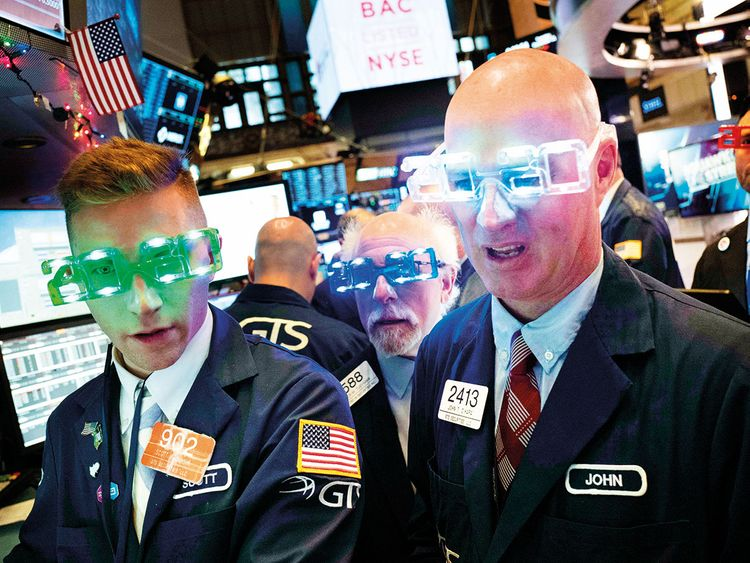 Traders wear New Year's 2020 party glasses at the New York Stock Exchange