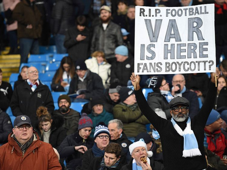 A Manchester City fan holds up a banner complaining about VAR.