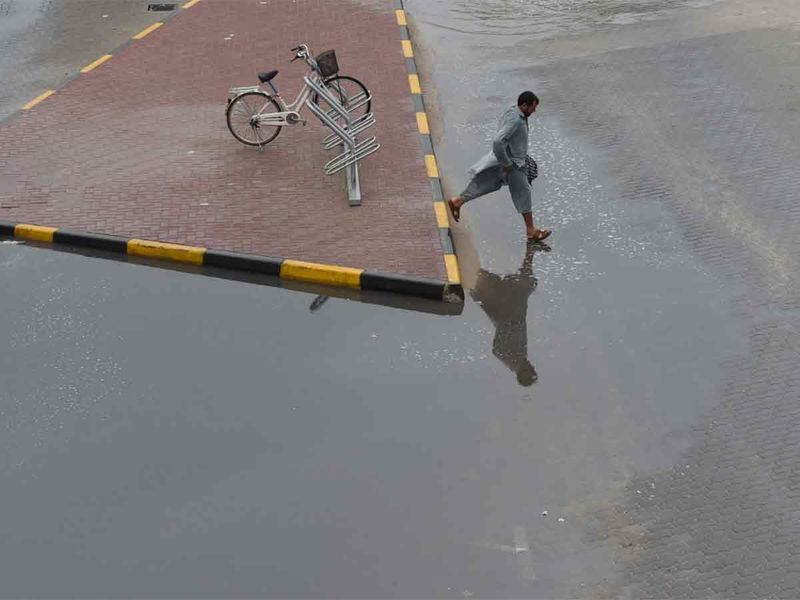 A man crossing the flooded water of over night rain in Ajman on 10 JAN 2020