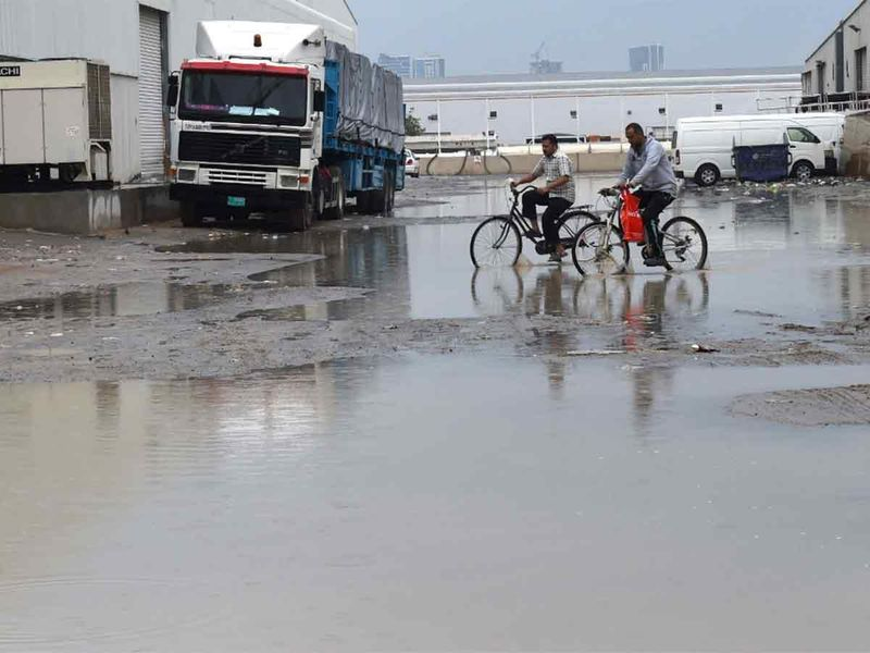 People on bicycles negotiating a flooded stretch in Ajman, on January 10, 2020.