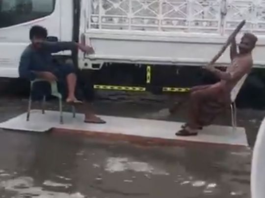 A wooden plank with two chairs used to raft through a waterlogged in the UAE
