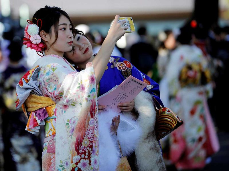 Japanese women wearing kimonos take selfies.