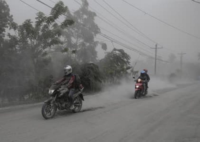 Motorcycles ride along an ash-covered road