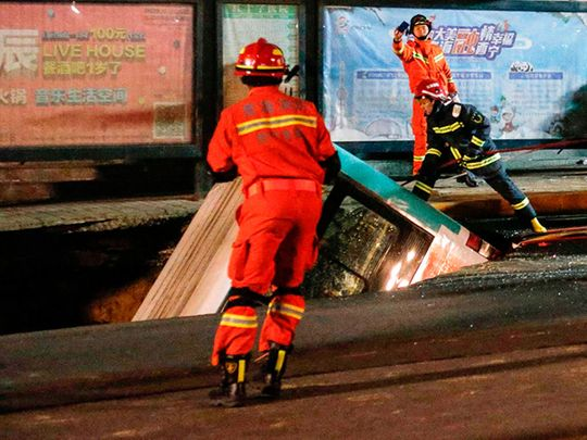 Rescuers preparing to lift a bus after a road collapse in Xining in China's northwestern Qinghai province.