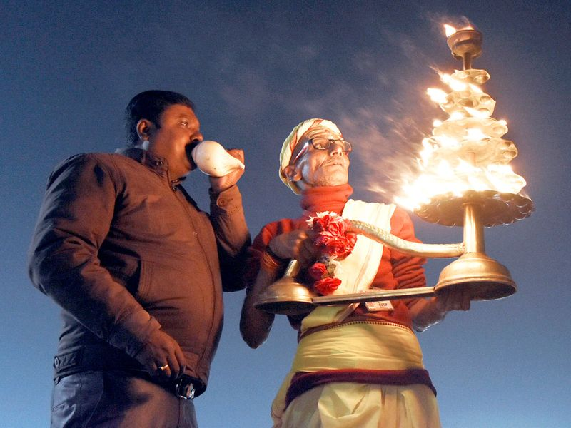 A priest performs Ganga Arti at Sangam on the occasion of Makar Sankranti festival during ongoing Magh Mela 2020 in Prayagraj