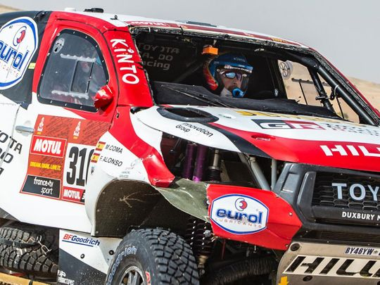 Fernando Alonso races through the Dakar Rally dunes after losing his windscreen while rolling his Toyota.